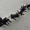 Tannenbaum, sapin coupé par un bûcheron. Tronçons reliés par des cardans de voiture. Ensemble peint au goudron. 500 x 80 x 80 cm, 2013